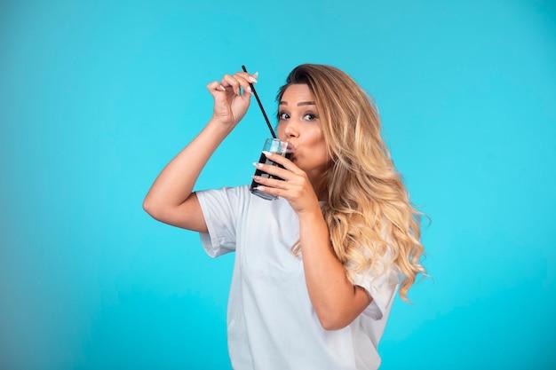 Giovane ragazza in camicia bianca, bere un bicchiere di cocktail nero.