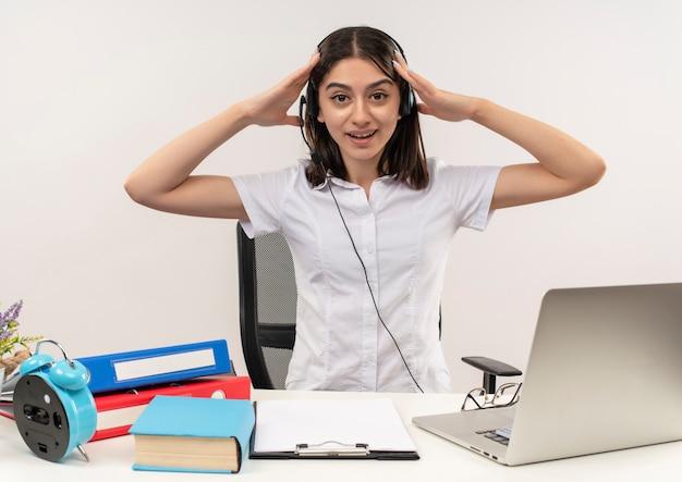 Giovane ragazza in camicia bianca e cuffie, tenendo la testa con le mani cercando confuso seduto al tavolo con cartelle e laptop sul muro bianco