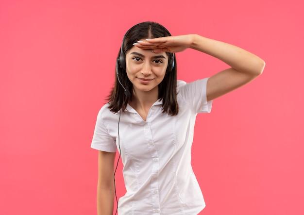 Giovane ragazza in camicia bianca e cuffie, guardando lontano con la mano sulla testa in piedi sul muro rosa