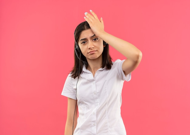 Giovane ragazza in camicia bianca e cuffie, guardando in avanti confuso con la mano sulla sua testa per errore in piedi sopra il muro rosa