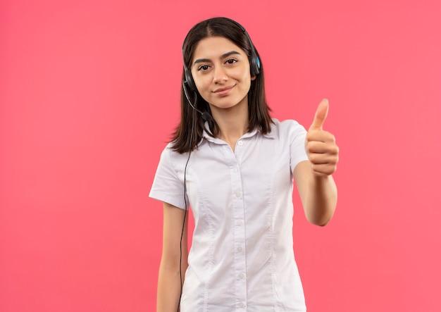Giovane ragazza in camicia bianca e cuffie, guardando in avanti sorridente che mostra i pollici in su in piedi sul muro rosa