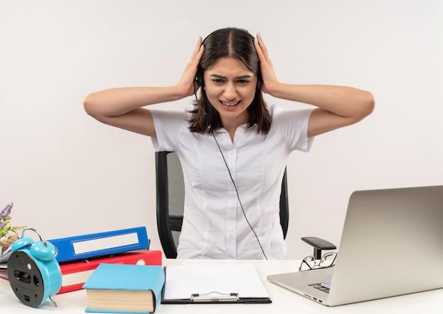 Giovane ragazza in camicia bianca e cuffie, guardando stanco e oberato di lavoro seduto al tavolo con cartelle e laptop sul muro bianco