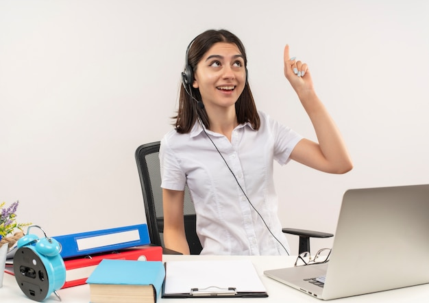Giovane ragazza in camicia bianca e cuffie, puntando con il dito indice in alto con grande idea seduto al tavolo con cartelle e laptop sul muro bianco