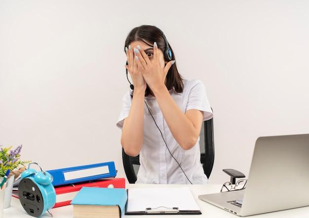 Giovane ragazza in camicia bianca e cuffie, spaventata che copre gli occhi con le palme che guardano attraverso le dita seduto al tavolo con cartelle e laptop sopra il muro bianco