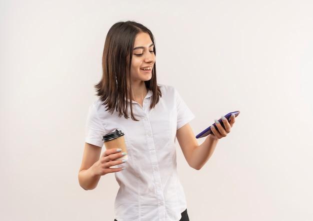 Giovane ragazza in camicia bianca tenendo la tazza di caffè guardando lo schermo del suo cellulare sorridendo allegramente in piedi sopra il muro bianco