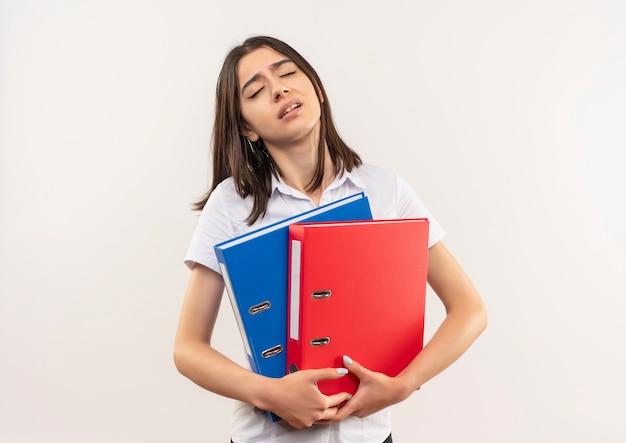Giovane ragazza in camicia bianca che tiene le cartelle che sembrano stanchi e annoiati in piedi sopra il muro bianco
