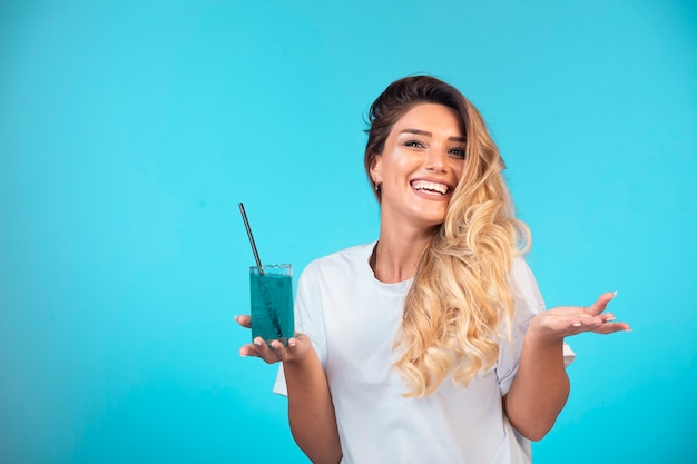 Young girl in white shirt holding a glass of blue cocktail and feels positive.