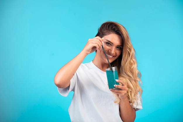 Giovane ragazza in camicia bianca con in mano un bicchiere di cocktail blu e si sente positiva