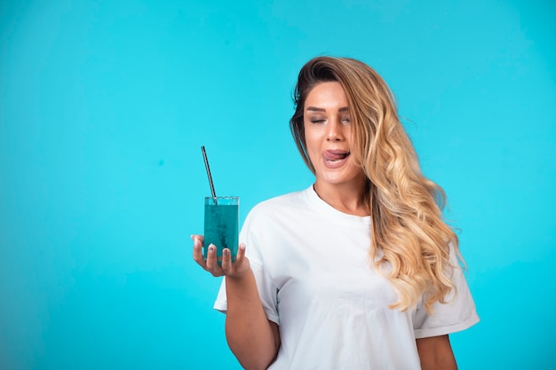 Young girl in white shirt holding a glass of blue cocktail and feels the taste.
