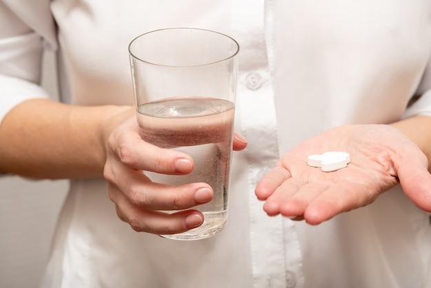 A young girl in a white shirt holds vitamins and a glass of water in her hands.