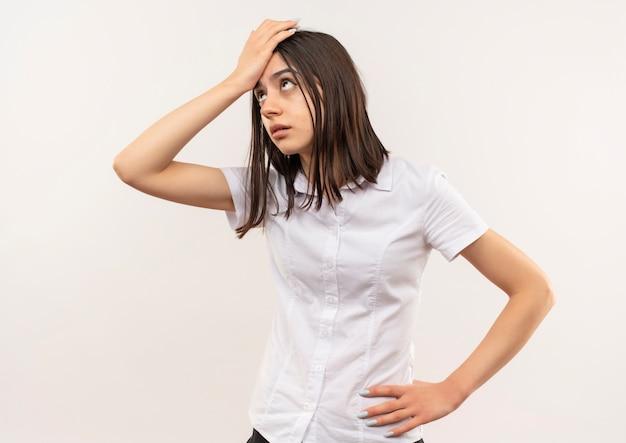 Giovane ragazza in camicia bianca che osserva da parte confusa con la mano sulla sua testa per errore in piedi sul muro bianco