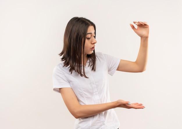 Giovane ragazza in camicia bianca che osserva da parte mostrando il gesto di dimensione con le mani, simbolo di misura in piedi sopra il muro bianco