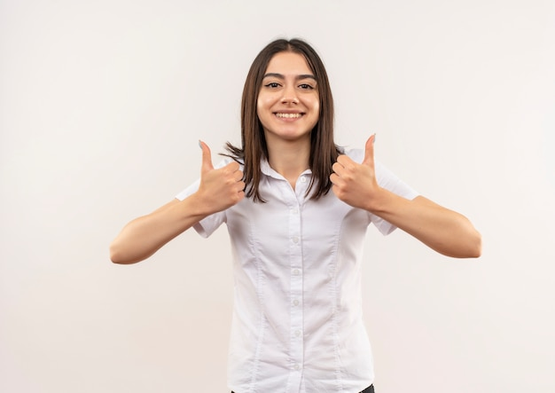 Giovane ragazza in camicia bianca guardando in avanti sorridendo allegramente mostrando i pollici in piedi sul muro bianco