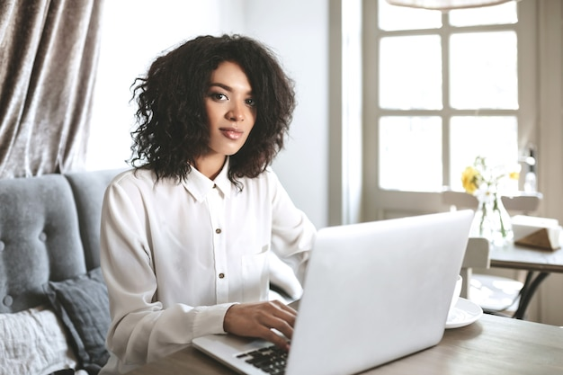 Young girl in white shirt sitting in restaurant with laptop. pretty african american girl with dark curly hair working on her laptop at cafe