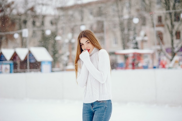 Young girl in a white sweater standing in a winter park