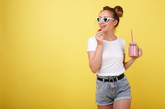 Young girl in a white t-shirt and glasses with strawberries and smoothies on a yellow space. summer mood
