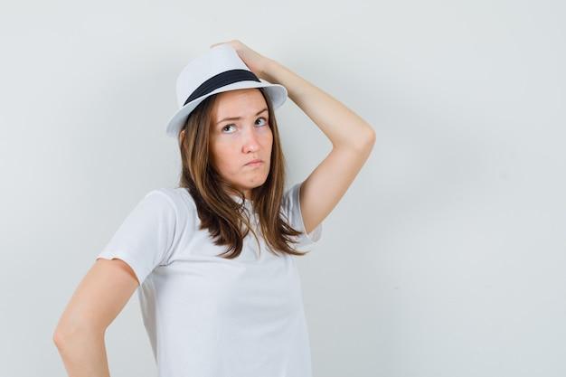Giovane ragazza in t-shirt bianca, cappello tenendo la mano sulla testa e guardando pensieroso, vista frontale.