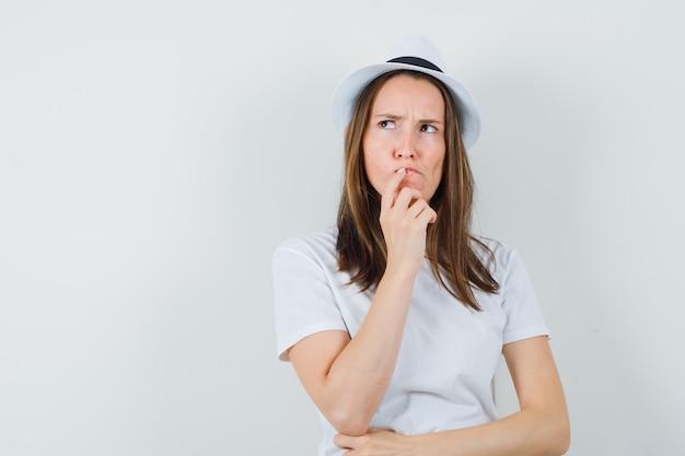 Giovane ragazza in t-shirt bianca, cappello tenendo la mano sulle labbra e guardando esitante, vista frontale.