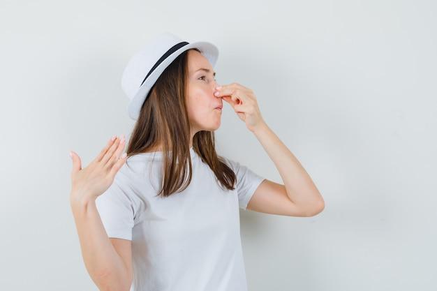Giovane ragazza in maglietta bianca, cappello che pizzica il naso a causa del cattivo odore e sembra disgustato, vista frontale.