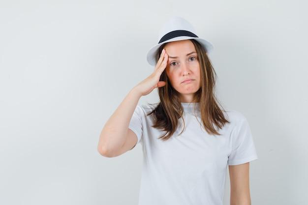 Giovane ragazza in maglietta bianca, cappello che tira la pelle sulle tempie e sembra triste, vista frontale.