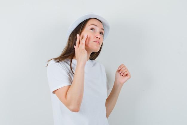 Giovane ragazza in t-shirt bianca, cappello che tocca la sua pelle del viso sulla guancia, vista frontale.