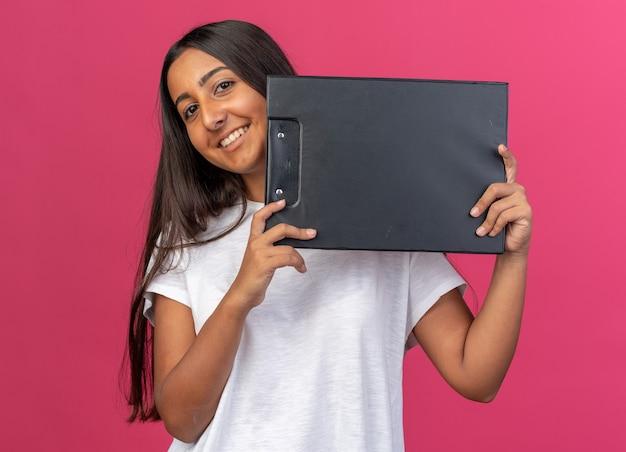 Giovane ragazza in maglietta bianca che tiene appunti guardando la telecamera sorridendo allegramente