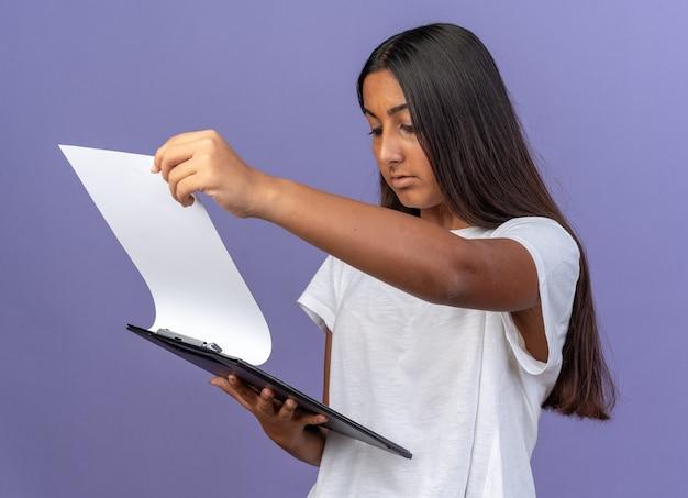 Giovane ragazza in maglietta bianca che tiene appunti con pagine bianche che lo guardano con una faccia seria in piedi su sfondo blu