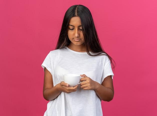 Giovane ragazza in maglietta bianca che tiene una tazza di caffè guardandola con una faccia seria
