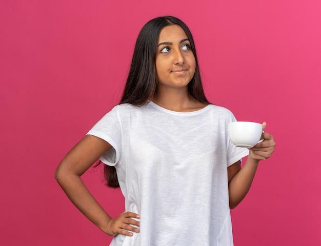 Giovane ragazza in maglietta bianca che tiene una tazza di caffè guardando in alto con un sorriso sul viso in piedi sopra il rosa