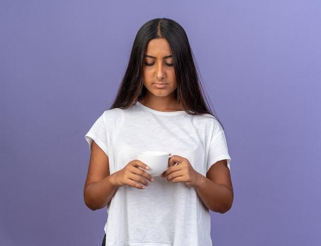 Giovane ragazza con una maglietta bianca che tiene in mano una tazza che la guarda con una faccia seria