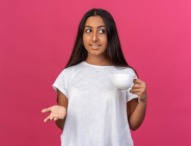 Giovane ragazza in maglietta bianca che tiene una tazza di tè che guarda da parte con un sorriso sul viso in piedi sopra il rosa