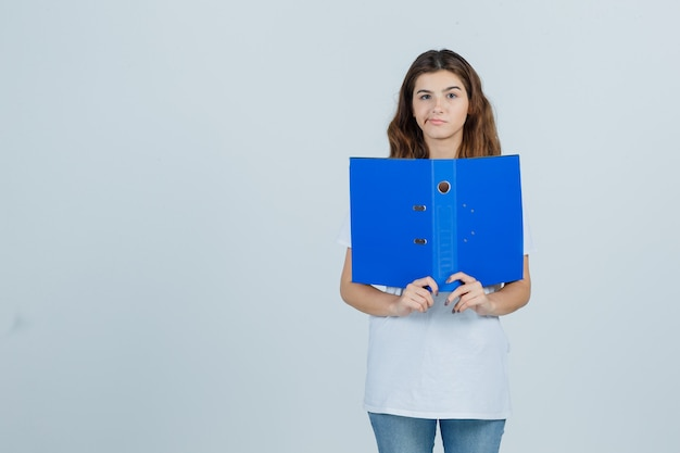 Young girl in white t-shirt holding folder, curving lips and looking disappointed , front view.
