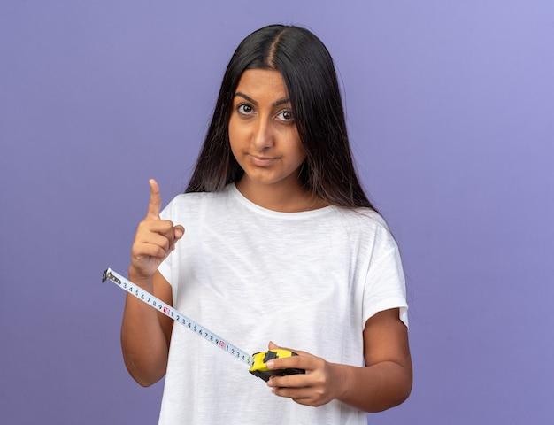 Giovane ragazza in maglietta bianca che tiene un metro a nastro che guarda la telecamera con una faccia seria che mostra un gesto di avvertimento del dito indice