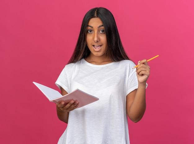 Ragazza in maglietta bianca che tiene taccuino e matita che guarda la macchina fotografica felice e sorpresa in piedi su sfondo rosa