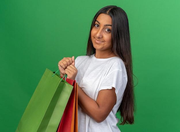 Giovane ragazza con una maglietta bianca che tiene in mano dei sacchetti di carta che guarda la telecamera felice e compiaciuta che sorride allegramente in piedi su uno sfondo verde