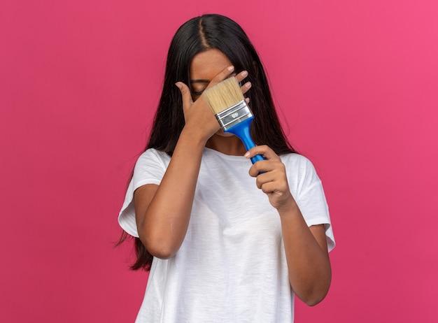 Giovane ragazza in maglietta bianca che tiene in mano un pennello da una pinta che copre gli occhi con la mano che sembra stanca e annoiata in piedi su uno sfondo rosa