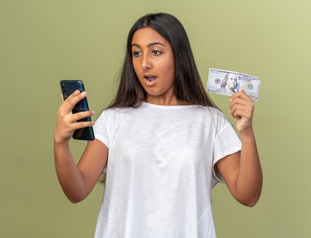 Young girl in white t-shirt holding smartphone and cash looking at screen of her mobile being surprised and happy