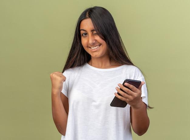 Giovane ragazza in t-shirt bianca che tiene in mano uno smartphone che stringe il pugno felice ed eccitata che sorride e fa l'occhiolino in piedi su sfondo verde
