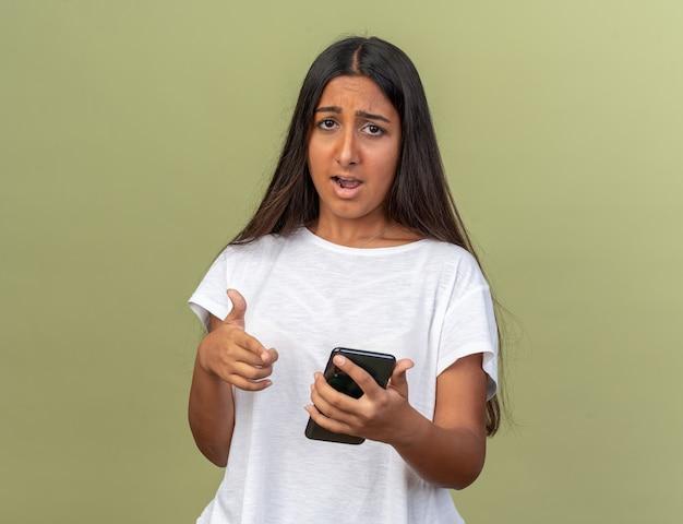 Giovane ragazza in maglietta bianca che tiene in mano uno smartphone che guarda la telecamera confusa e molto ansiosa