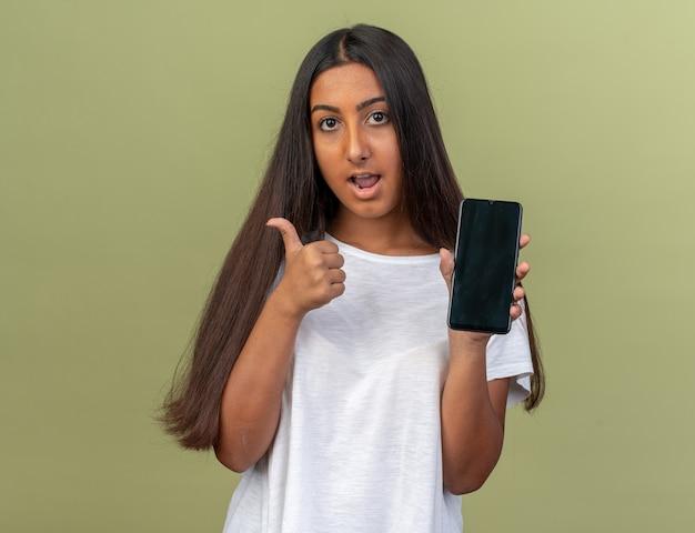 Ragazza in maglietta bianca che tiene smartphone che guarda l'obbiettivo sorridente fiducioso che mostra i pollici in su