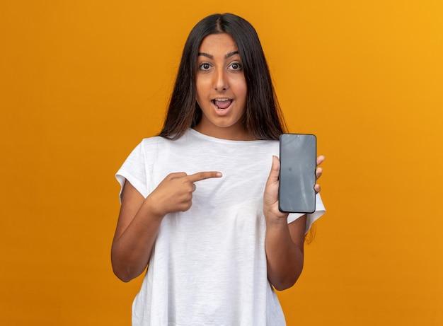 Ragazza in maglietta bianca che tiene smartphone che punta con il dito indice sorridendo