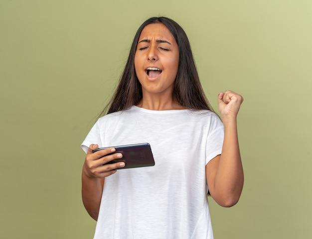 Ragazza in maglietta bianca che tiene smartphone alzando il pugno felice ed eccitata in piedi su sfondo verde