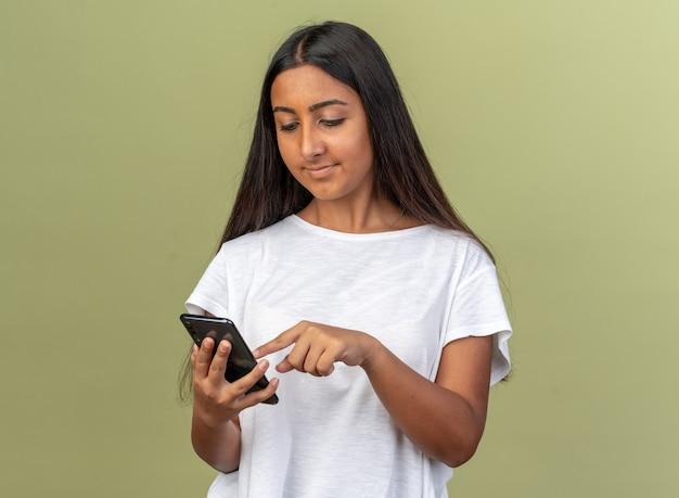 Ragazza in maglietta bianca che tiene smartphone che scrive un messaggio che sembra sicura in piedi su sfondo verde