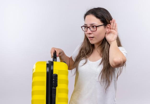 Giovane ragazza in maglietta bianca che tiene la valigia da viaggio tenendo la mano vicino all'orecchio cercando di ascoltare la conversazione di qualcuno