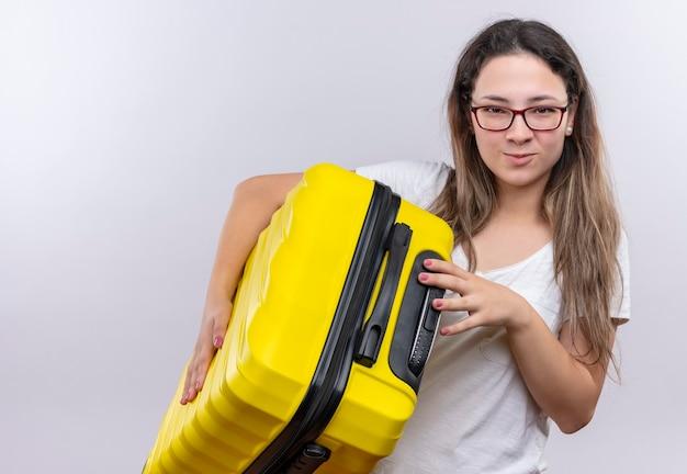Giovane ragazza in t-shirt bianca che tiene la valigia di viaggio che sembra sorridere fiducioso