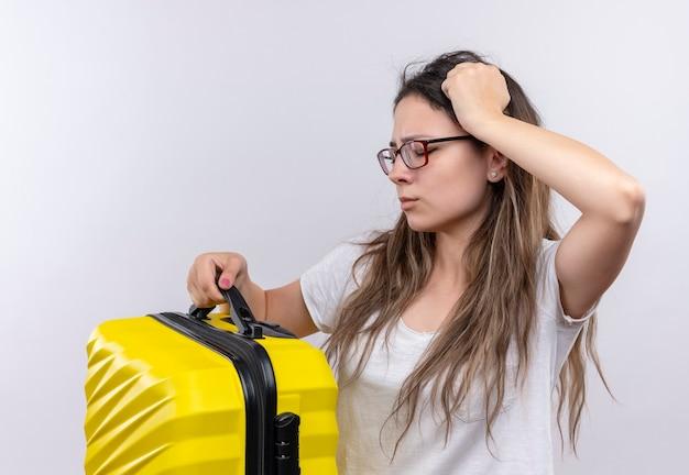 Giovane ragazza in t-shirt bianca che tiene la valigia di viaggio che sembra testa commovente confusa e molto ansiosa