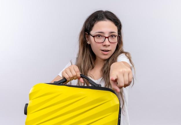 Giovane ragazza in t-shirt bianca che tiene la valigia di viaggio che sembra sorpreso che indica con il dito indice alla macchina fotografica