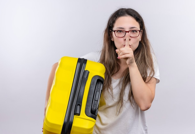 Giovane ragazza in t-shirt bianca che tiene la valigia da viaggio facendo gesto di silenzio con il dito sulle labbra
