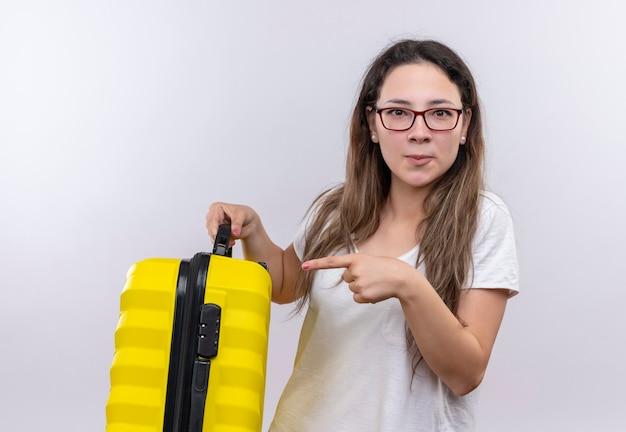 Giovane ragazza in maglietta bianca che tiene la valigia di viaggio che indica con il dito dispiaciuto