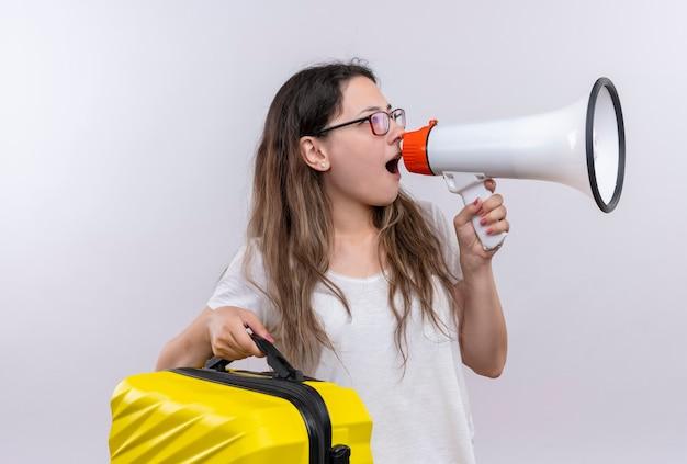 Giovane ragazza in maglietta bianca che tiene la valigia di viaggio che grida al megafono